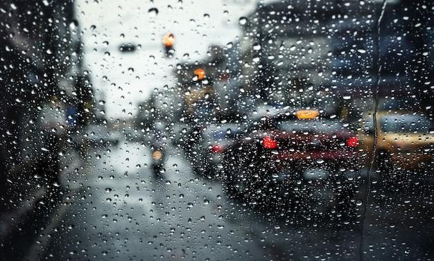 Traffico mattutino in una giornata piovosa, vista attraverso il parabrezza durante la tempesta di pioggia con messa a fuoco selettiva.