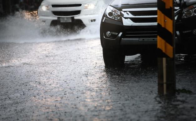 Traffico mattutino in una giornata piovosa con pioggia battente e inondazione in città, messa a fuoco selettiva.
