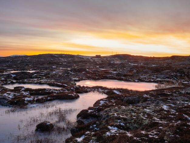 Vista la mattina di belle pozzanghere ghiacciate e muschi sul pendio roccioso della montagna da vicino