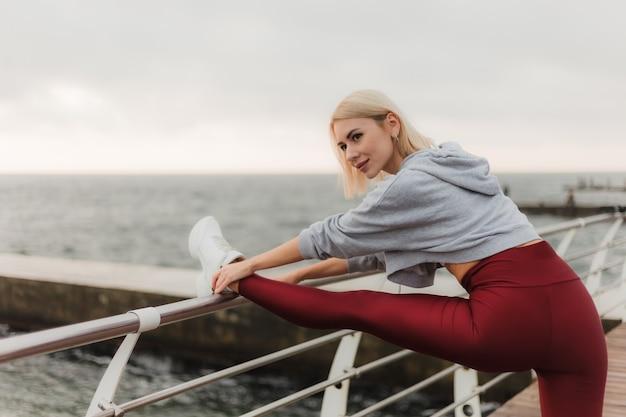 Allenamento mattutino concetto di stile di vita sano giovane donna attraente in abiti sportivi fa stretching delle gambe