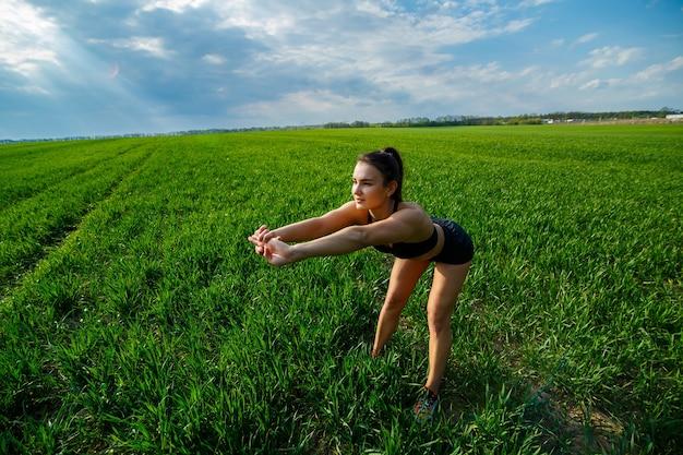 Allenamento mattutino. concetto di stile di vita sano. la giovane donna attraente in abiti sportivi fa allungare la sua mano prima dell'allenamento sulla natura all'alba. riscaldamento muscolare