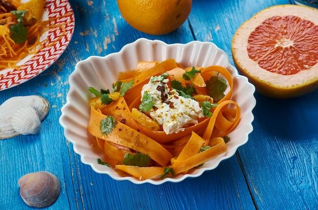 Cucina marocchina, insalata di carote harissa con formaggio feta, piatti tradizionali marocchini assortiti, vista dall'alto.