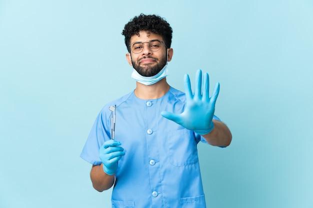 Uomo marocchino del dentista che tiene gli strumenti sull'azzurro che conta cinque con le dita