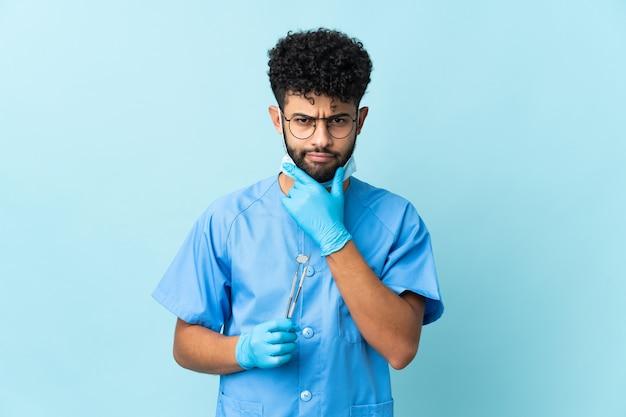 Uomo marocchino dentista che tiene strumenti isolati sul pensiero blu