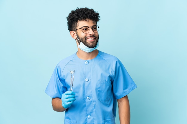 Uomo marocchino dentista che tiene strumenti isolati sulla parete blu in posa con le braccia all'anca e sorridente