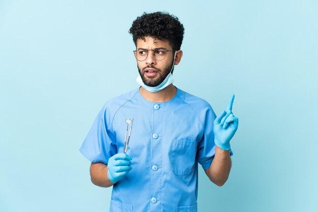 Uomo marocchino del dentista che tiene gli strumenti isolati sulla parete blu che pensa un'idea che indica il dito verso l'alto