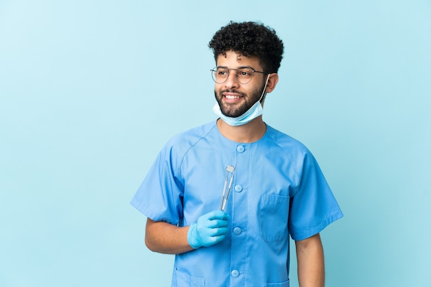 L'uomo marocchino del dentista che tiene gli strumenti ha isolato pensando un'idea mentre osservava