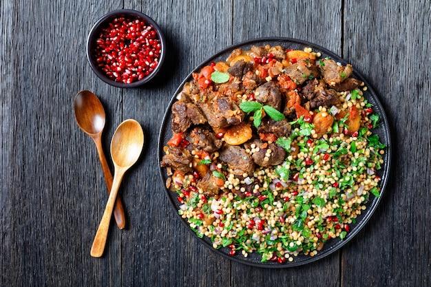 Stufato di agnello marocchino con cous cous di perle alle erbe e semi di melograno su una piastra nera su un tavolo di legno scuro, vista orizzontale dall'alto, piatto, spazio libero