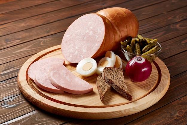 Mortadella con verdure ed erbe aromatiche su un piatto di legno su un tavolo di legno.