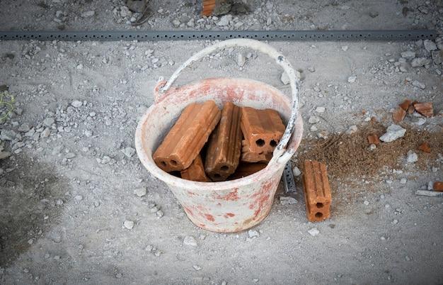 Secchio di mortaio pieno di mattoni