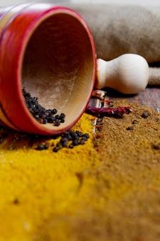 Mortaio e pestello vicino al cucchiaio bianco con differente delle spezie sparse sulla tavola di legno