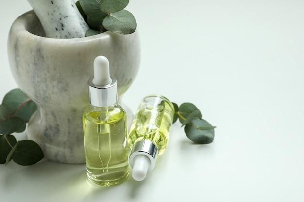 Mortaio con eucalipto e flaconi contagocce di olio su sfondo bianco