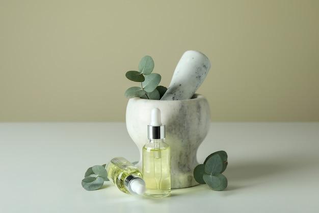 Mortaio con eucalipto e flaconi contagocce di olio sul tavolo bianco