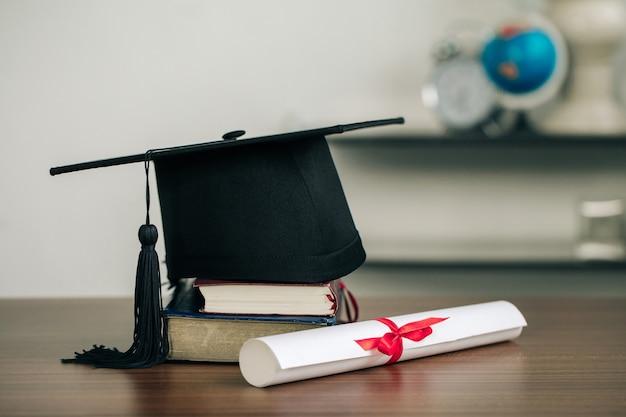 Un mortarboard su libri e una pergamena di laurea sulla scrivania.concetto di apprendimento dell'istruzione