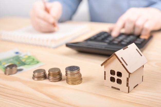 Calcolatore di mutuo ipotecario. la mano del maschio ha messo la scala dei soldi della pila della moneta sul tavolo, il concetto di crescita aziendale
