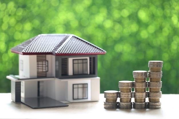 Mutuo, casa modello e pila di monete soldi su sfondo verde naturale, investimento aziendale e concetto di bene immobile