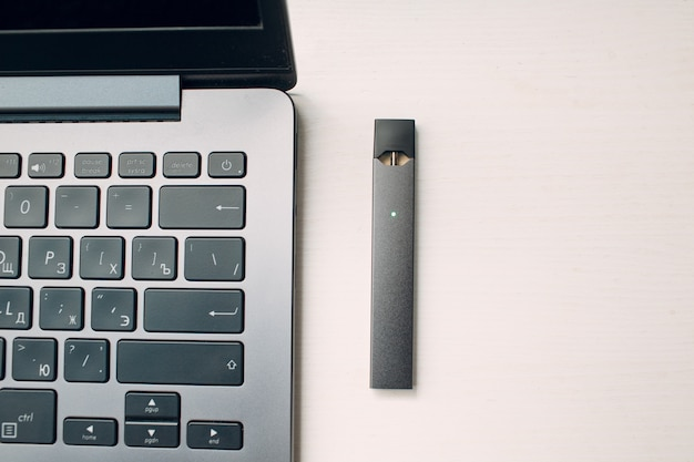 Mosca - 26 giugno 2020: bastone e laptop per vapori di nicotina con sigaretta elettronica juul.