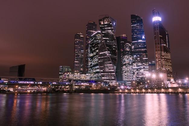 Vista notturna della città di mosca con grattacieli e un ponte futuristico sul fiume
