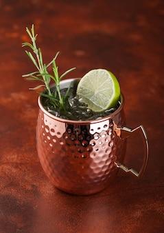 Cocktail di mulo di mosca in una tazza di rame con lime e rosmarino sul tavolo marrone