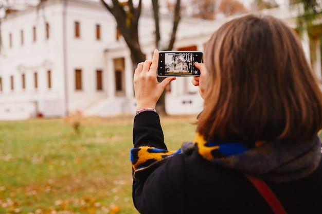 Mosca, russia, ottobre 2019 - una donna viaggiatrice in abiti autunnali alla moda scatta foto dell'edificio immobiliare nel parco autunnale sul suo smartphone. concetto di viaggio locale. vista posteriore sopra la spalla