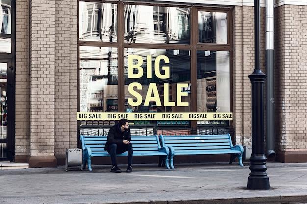 Mosca / russia - ottobre 2019: un giovane seduto su una panchina davanti alla vetrina di un negozio che pubblicizza una grande vendita. giovane donna nella finestra a guardare le merci