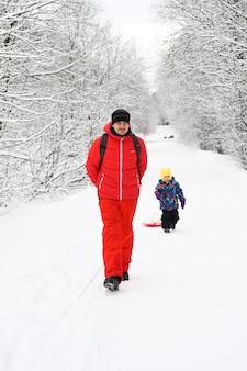 Mosca / russia - gennaio 2020: famiglia felice con bambini si diverte a trascorrere le vacanze invernali nella foresta invernale innevata. padre gioca con suo figlio