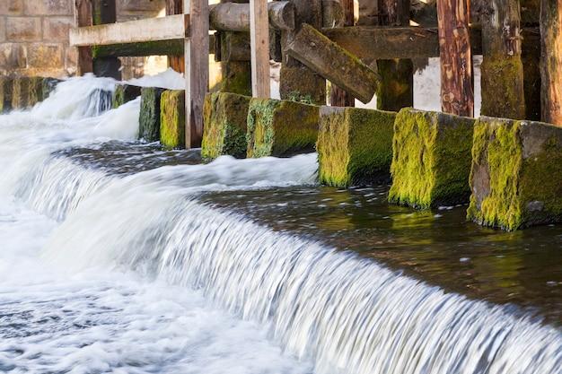 Vecchi infissi coperti di muschio e le fondamenta della vecchia diga. primo piano rappresentato graficamente, piccola profondità di campo. la struttura presenta un foro attraverso il quale scorre l'acqua