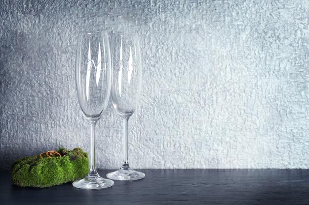 Muschio con fedi nuziali e bicchieri di champagne sul tavolo e sfondo grigio muro