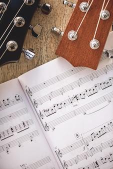 La più bella musica per chitarra. vista ravvicinata dei colli della chitarra e delle note musicali contro uno sfondo di legno. strumenti musicali. attrezzature musicali