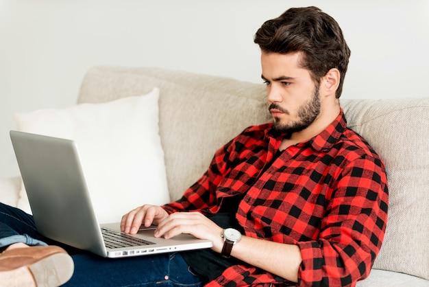 Il posto più comodo per lavorare. giovane serio che lavora al computer portatile mentre è seduto sul divano