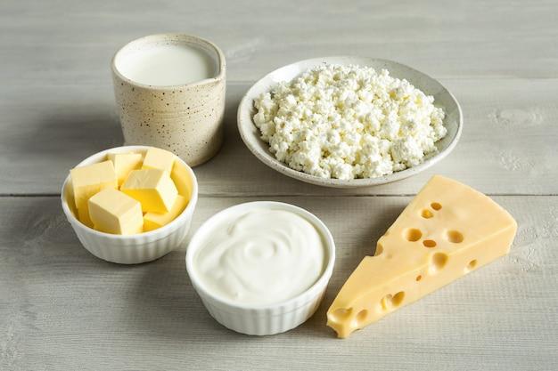I prodotti lattiero-caseari più comuni sono burro, formaggio, latte, panna acida, ricotta in un piatto bianco su un fondo di legno bianco da vicino. alimenti naturali e biologici.