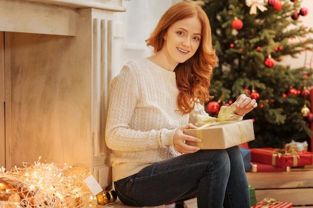 Il periodo più emozionante dell'anno. affascinante signora rossa seduta accanto a un caminetto decorativo e apre un piccolo regalo.