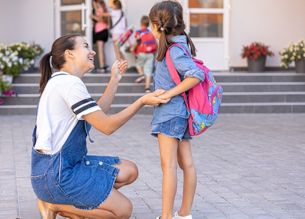 Una madre accompagna lo studente a scuola, bambina felice con una mamma premurosa, torna a scuola.