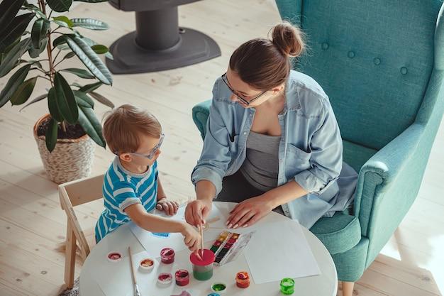 Madre o terapista dell'arte e bambino dipingono insieme l'acquerello