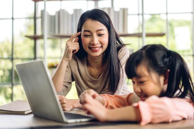 Madre e bambino asiatico bambina che impara e guarda il computer portatile che fa i compiti studiando la conoscenza con il sistema di e-learning di formazione online. videoconferenza per bambini con insegnante tutor a casa