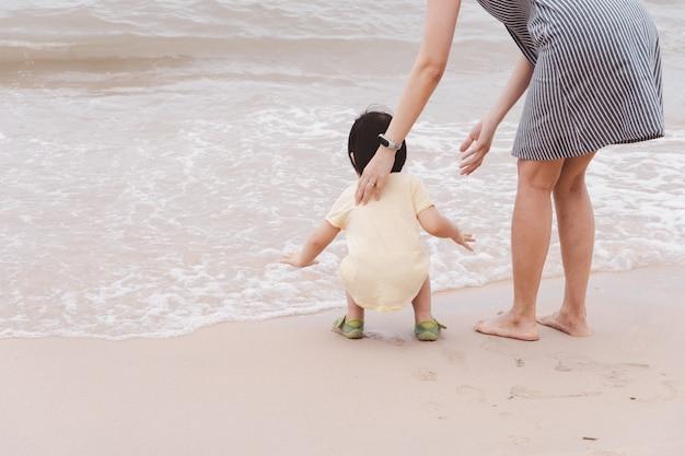 Madre e bambino asiatico che giocano sulla spiaggia.