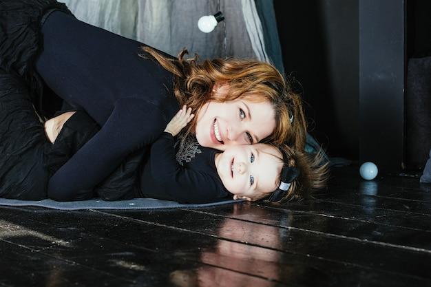 Madre e figlia felice e bella a casa in un corpo nero alla moda