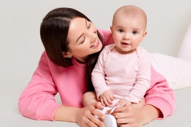 Madre e bambino che giocano insieme, bambino carino seduto sul pavimento che indossa una tuta, mamma che abbraccia il suo bambino e la guarda con amore e sorriso gentile, famiglia felice.