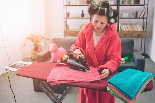 Madre e bambino insieme impegnati nei lavori domestici stiratura dei vestiti. casalinga e bambino che fanno i compiti