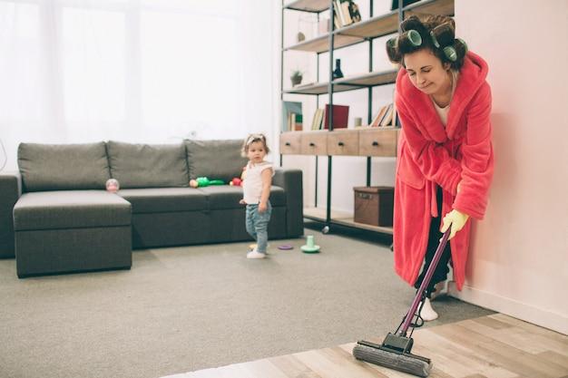 Madre e bambino insieme impegnati nelle faccende domestiche. sta lavando il pavimento della scopa. casalinga e bambino a fare i compiti. donna con bambino piccolo in salotto. casalinga che fa molti compiti mentre guarda