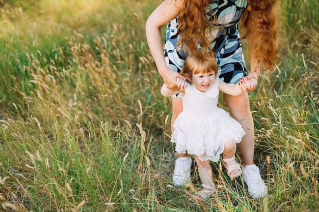 La madre si china su sua figlia e la tiene per le braccia.