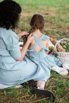La madre in vestito blu intreccia i capelli delle sue figlie