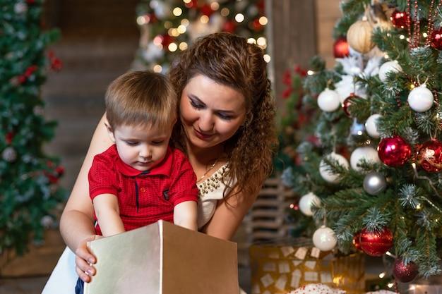 Madre e ragazzo sotto l'albero di natale con regali. donna con bambino per capodanno