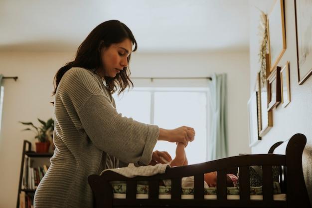 Mamma che cambia un pannolino su un neonato