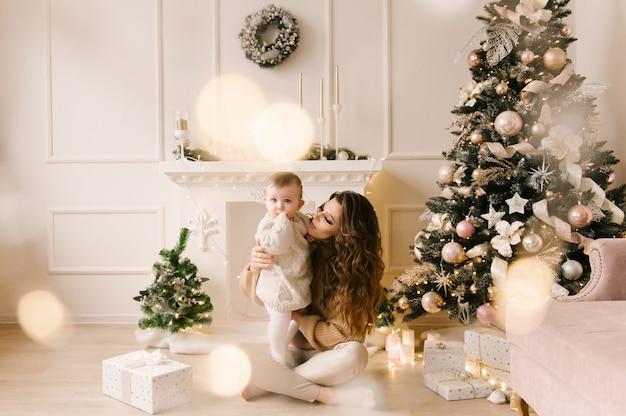 Madre e figlio la mattina di natale all'albero di natale con regali