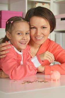 Madre e figlia che mettono le monete nel salvadanaio