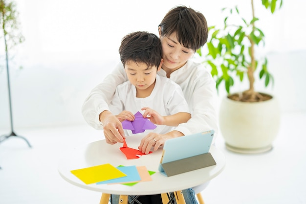 Madre e figlio che fanno origami mentre guardano un tablet pc