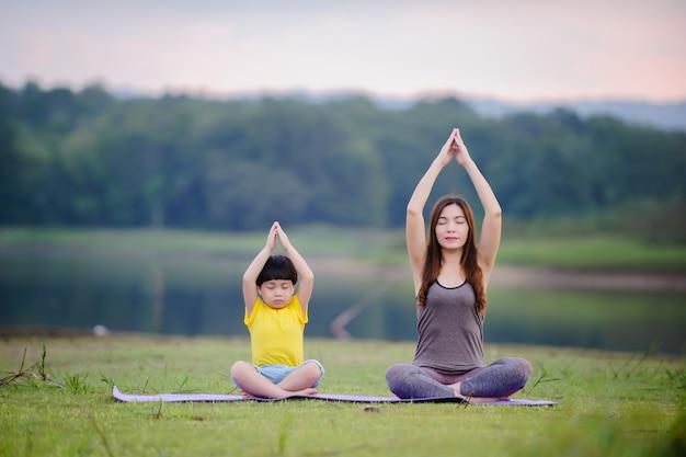 Madre e bambino che fanno esercizi di yoga sull'erba al parco prima del tramonto in estate.