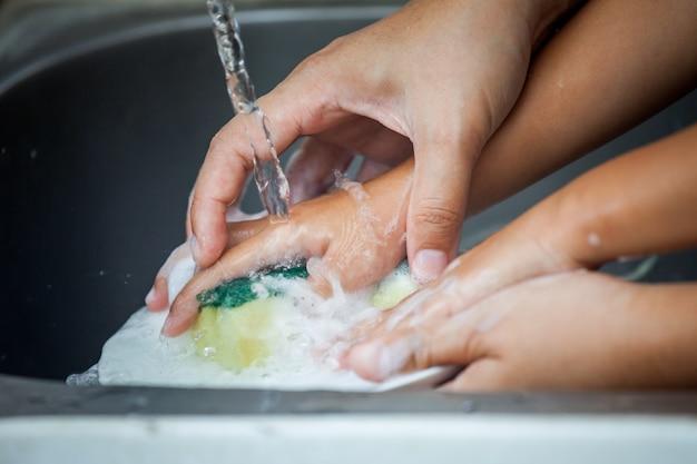 La mano della madre e del bambino lava i piatti sopra il lavandino in cucina insieme