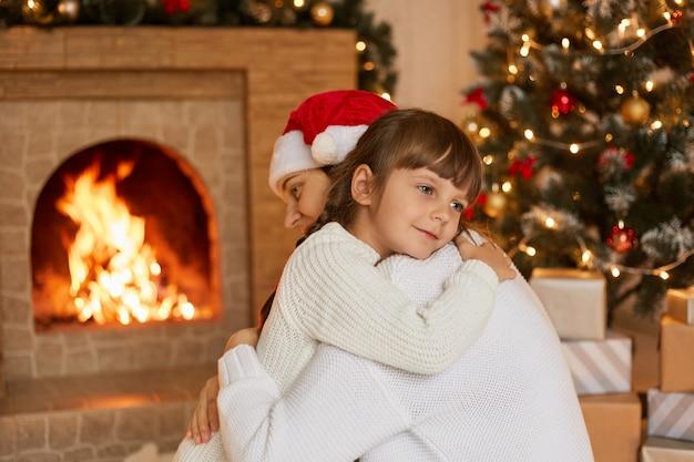Madre e bambino abbracci la sera d'inverno davanti al caminetto, sognante bambino femmina che indossa un maglione bianco essendo soddisfatto trascorrere la vigilia di natale con la mamma